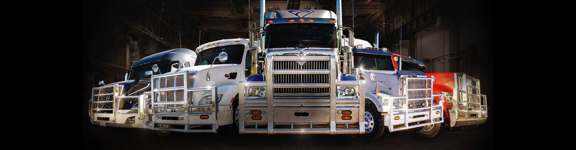 five semi trucks of varying manufactures with herd truck guards